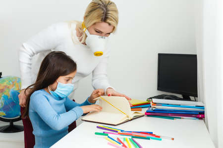 mother and daughter in protective mask do homework at distance home schooling, quarantine