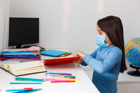 little girl in a protective mask at distance home schooling, quarantine Imagens