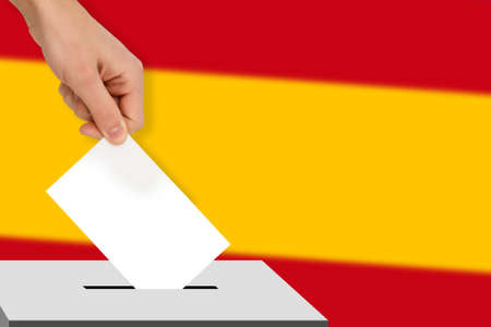hand drops the ballot election against the background of the spain flag, concept of state elections, referendum