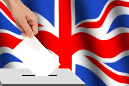hand drops the ballot election against the background of the flag, concept of state elections, referendum