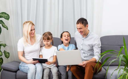 Young joyful casual family of two kids and couple sitting on sofa and watching funny video or cartoons in touchpad Stock Photo