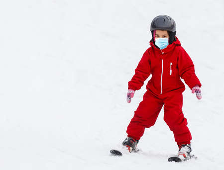 Portrait of a little girl skier in medical mask during COVID-19 coronavirus on a snowy mountain at a ski resort