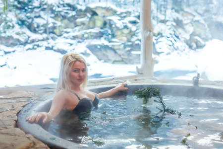 Young lady relaxing outside in thermal bath in winter