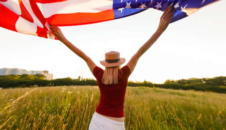 Beautiful young girl holding an American flag in the wind in a field of rye. Summer landscape against the blue sky. Horizontal orientation. Stock Photo