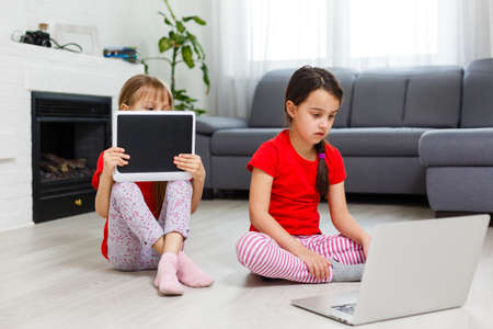 Little girls playing on a tablet computing device sitting on the floor