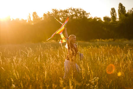 Portrait of a young and carefree woman launching kite on the greenfield. Concept of active lifestyle in nature
