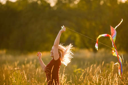 Beauty girl running with kite on the field. Beautiful young woman with flying colorful kite over clear blue sky. Free, freedom concept. Emotions, healthy lifestyle