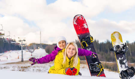 mother and daughter with snowboards in a mountain resort