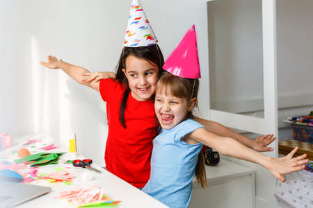 A little girl, curves and laughs in front of a laptop in a cap. Celebrates birthday via internet in quarantine time, self-isolation and family values, online birthday. Congratulations to the animator