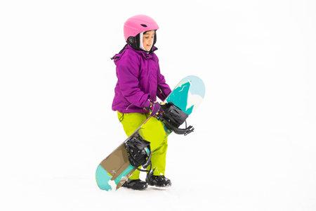 Little Cute Girl Snowboarding at ski resort in sunny winter day.
