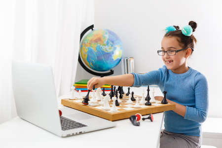Portrait Caucasian Little cirly girl playing chess at the table in interior with chessboard. little girl learns chess on a laptop online