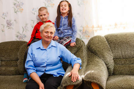 Grown up adult smiling grandchildren embraces elderly grandmother glad to see missing her, visit of loving relatives enjoy communication, cuddle as symbol of connection, love and support concept