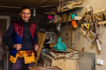 Satisfied cheerful joyful smiling woodmaster is standing near desktop in his workshop, workstation