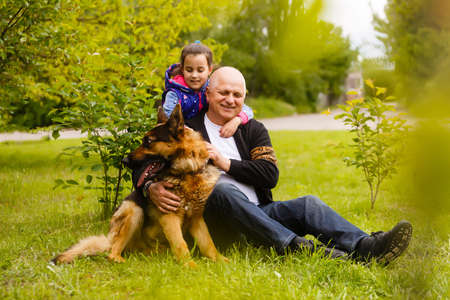 Grandfather And Granddaughter Taking Dog For Walk