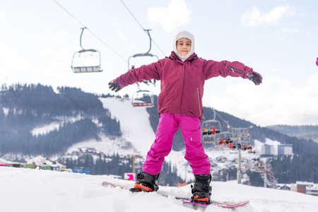 smiley happy little girl with snowboard at winter outdoor