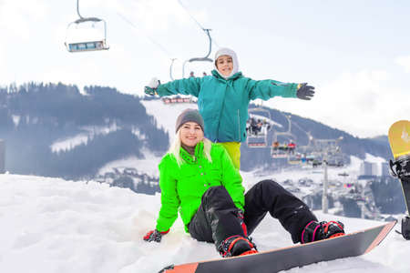 Mother and daughter with snowboards are playing in the snow