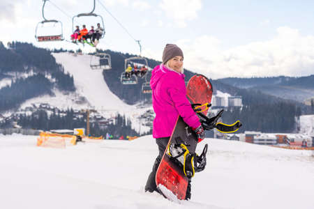 Young woman holding snowboard at winter resort