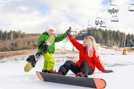 mother and daughter with snowboards at winter resort