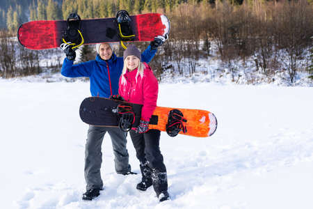 family with snowboards at winter resort