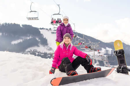 Young mother and daughter with snowboards at winter resort