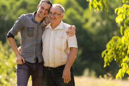 Portrait of a smiling father with adult son at the park Standard-Bild