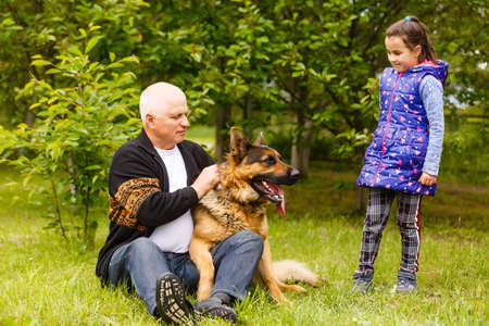 Grandfather and granddaughter relaxing with dog