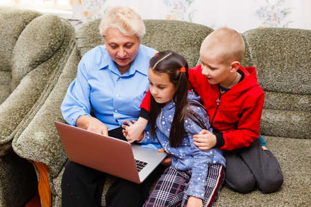 Grandmother with grandchildren using laptop at home
