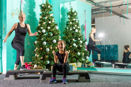mother and daughter doing fitness near the christmas tree at gym. New Year. Christmas, holidays, fitness, and gym concept.