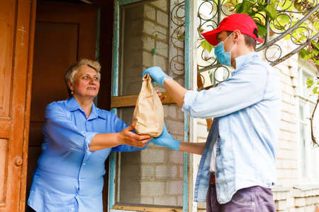Young male volunteer in mask gives an elderly woman boxes with food near her house. Son man helps a single elderly mother. Family support, caring. Quarantined, isolated. Coronavirus covid-19. Donation