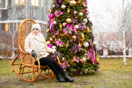 woman and photo zone christmas tree and rocking chair on the street