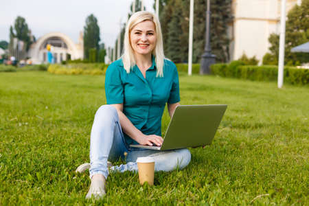 beautiful young blond woman with a laptop in the park on a warm summer day Stok Fotoğraf