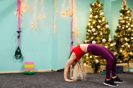 young woman goes in for sports near christmas tree at the gym