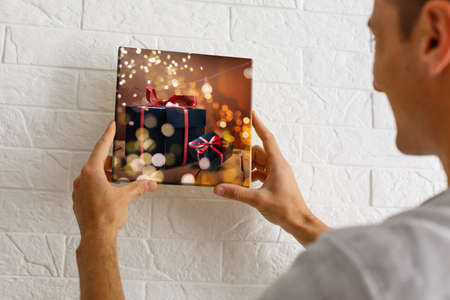 man holds photo canvas at home 写真素材