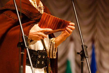 Musician playing panpipe. Musical instrument rondador or pan flute. Man playing flute during ethnic music concert