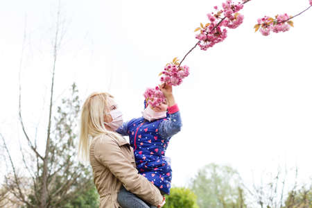 A European mother in a respirator with her daughter are standing near flowering tree. protective mask to save herself from virus. Standard-Bild
