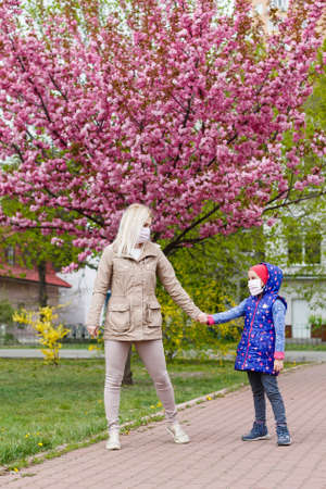 Mother and daughter with masks walking and talking on the street Standard-Bild