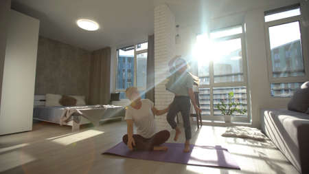 Mother and daughter doing fitness exercises on mat at home Standard-Bild