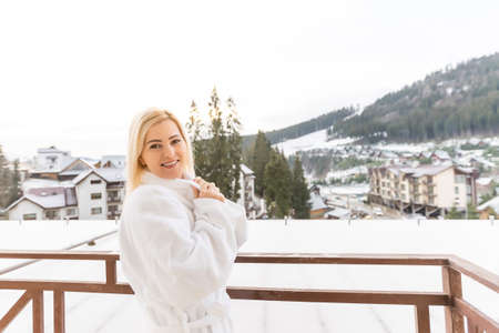 Charming healthy young blonde woman bathrobe walks barefoot on her large terrace enjoying the winter nature. Concept vacation in own big country house or hotel