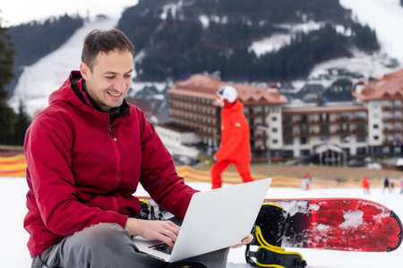 snowboarder typing on the laptop in the mountains winter Standard-Bild