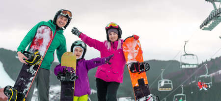 Portrait of happy family with snowboards looking at camera on blue background