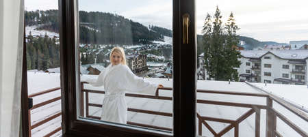 Young woman with a view of the winter mountain landscape Standard-Bild
