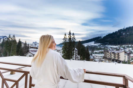 A woman in a white bathrobe standing on the balcony of a SPA in Austria in winter. She has wet hair. She is enjoying the view on mountains in front of her. She is feeling relaxed