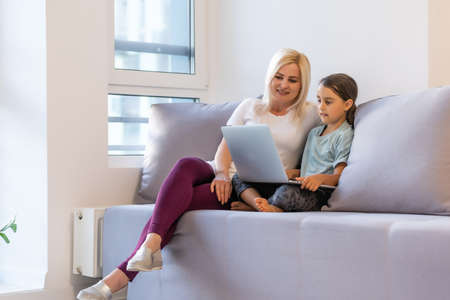 Beautiful woman helping her daughter doing her homework at home