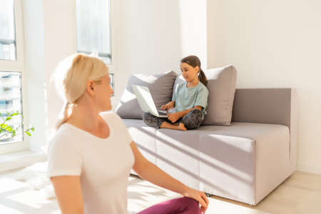 mother and daughter make yoga exercise online with laptop at home