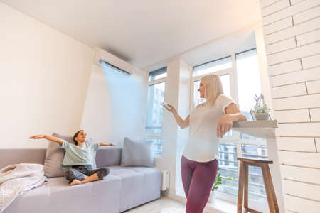 Happy family under air conditioner, mom holding remote control switch on conditioning in living room adjust comfort temperature for daughter, climate system at modern home