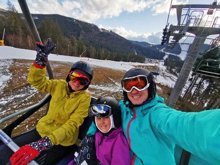 Family enjoying skiing on sunny winter day Standard-Bild