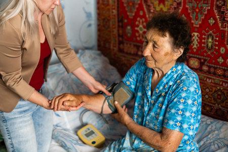Elder woman having measured blood pressure by cardiologist