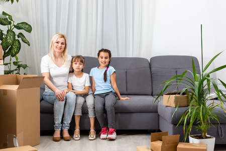 Mother and daughters packing cardboard boxes at home