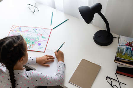 children, education and learning concept - student girl with book writing to notebook at home