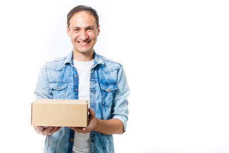smiling delivery man holding a big parcel isolated on white